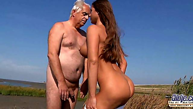 Old guy seduced and fucked by a nympho busty girl on the beach