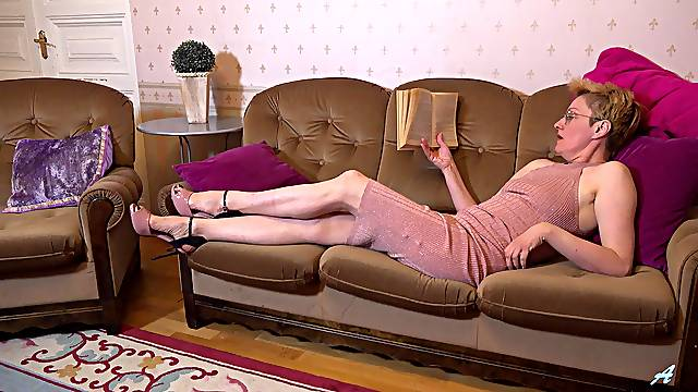 Mature sits on the couch and moans for a bit of sexual pleasure