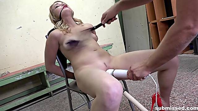 Blonde slave Rebecca Black tied up to a chair and pleasured