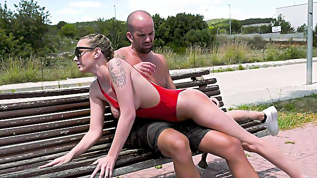 Dressed in a red swimsuit, Lya Missy fucks on a public park bench