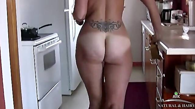 Housewife cleans the kitchen in the nude