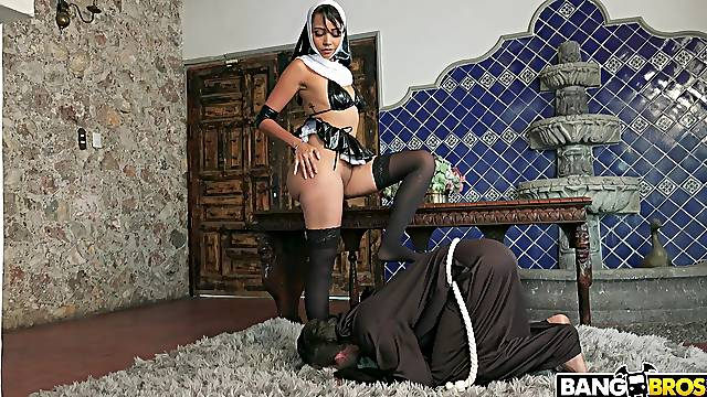 Seductive nun in domination role play with slave man