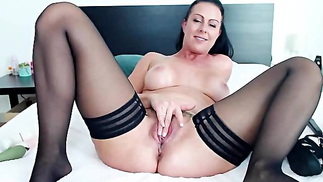 Busty German MILF teases viewers and masturbates on the bed