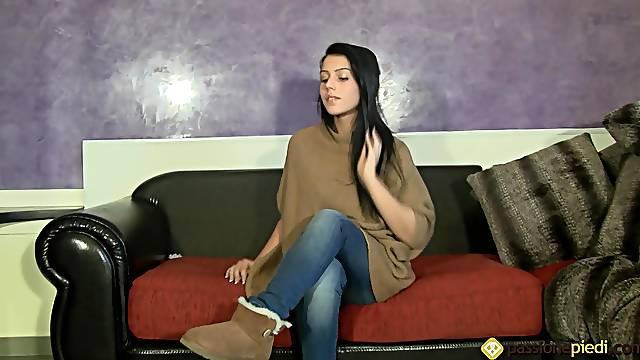 Solo brunette in jeans showing her feet wearing a nylon socks
