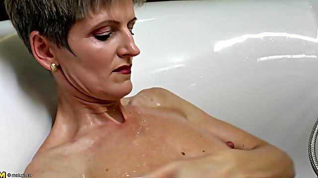 Skinny mature woman with a sexy body masturbating in the bath tub