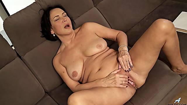 Amateur mature wife Olivia Westervelt moans while masturbating on the sofa