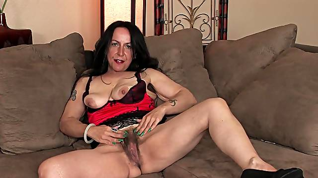 Kinky MILF Nina Swiss loves teasing with her hairy pussy on the couch