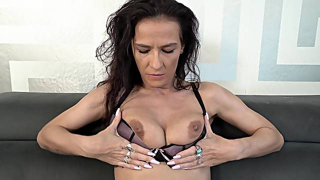 Horny solo mature spreads her legs and inserts a dildo in her cunt