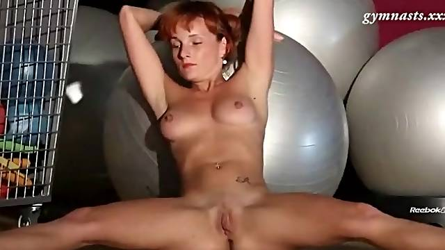 Redhead stretches naked in the gym