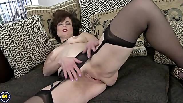 Classy granny in stockings and a garter belt masturbates