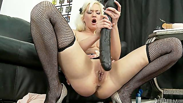 Chick in fishnets fucks a huge dildo into her cunt