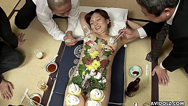 Japanese business men eat food off a beautiful girl