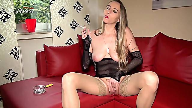 German milf Natalie smoking and playing with her pussy on the couch