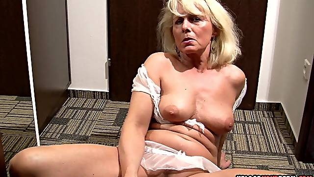 Blonde mature with big tits spreads her legs and fingers herself with passion.