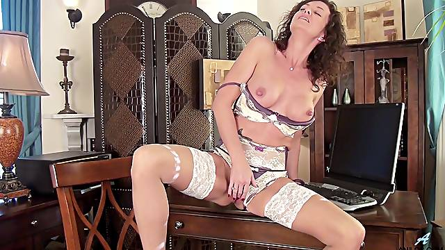 Mature model Lucy Heart opens her legs to play with her shaved pussy