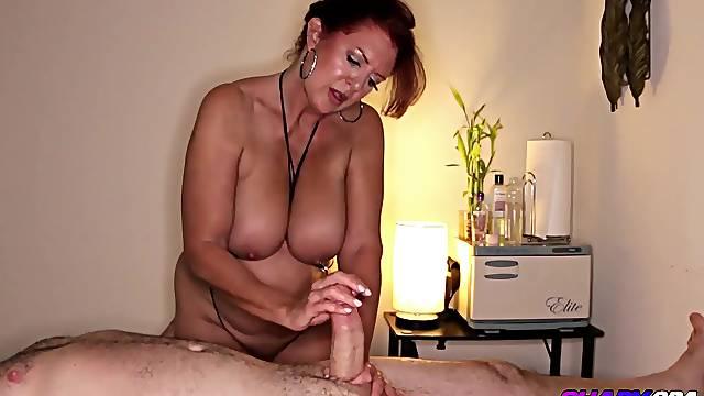 Redhead MILF giving an oily body rub that turns into a happy ending handjob