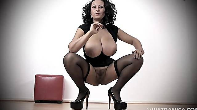 Busty MILF Danica Collins in stockings and high heels playing