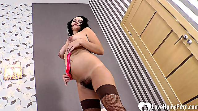 MILF strips off everything but her stockings and high heels before masturbating.