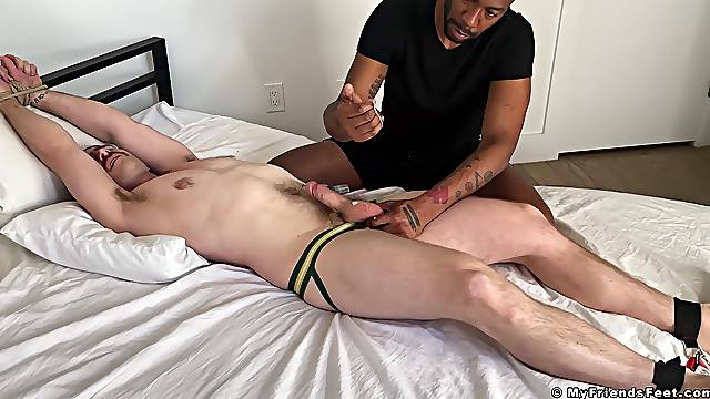 Tied up gay dude likes it when a black guy plays with his dick