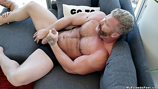 Horny gay dude jerking off his cock while a friend sucks on his toes