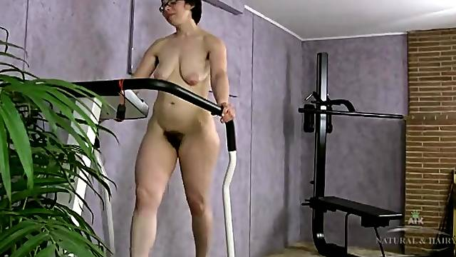 Hairy girl on the treadmill for a walk and striptease