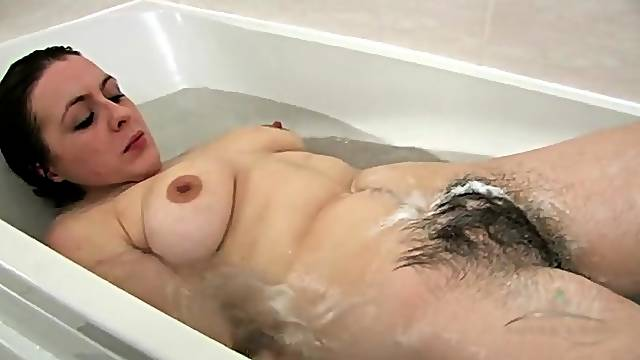 Washing her hairy legs and pussy in the bathtub