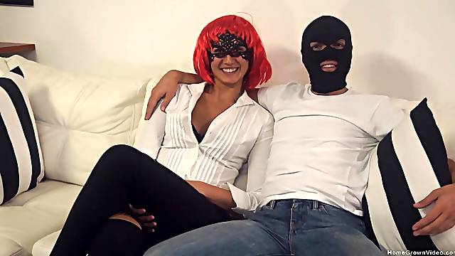 Gal in a vibrant red wig and a masked man do it up in style