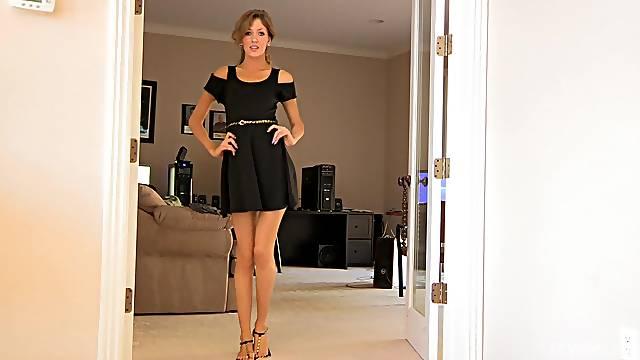 Cute trophy wife dressed in a black dress enjoys teasing. HD